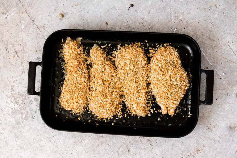 the uncooked parmesan crusted chicken tenders in a cooking pan