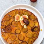 A plate Upside Down Fresh Fig Cake on aplate with flowers and a fig