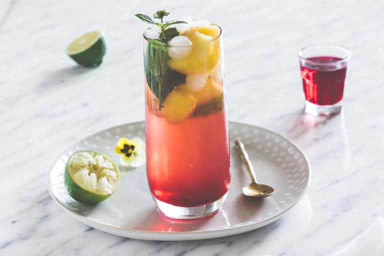 A glass of Hibiscus Whisky Sour a garnished with lime, mango chunks and mint.