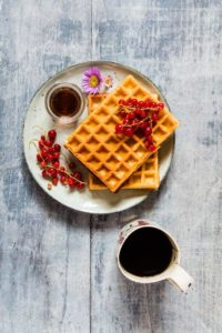 overhead shot of honey waffles on a plate with blue rim next to a cup of coffee