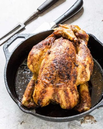 Roast nutmeg orange chicken recipe in a skillet with carving utensils next to it