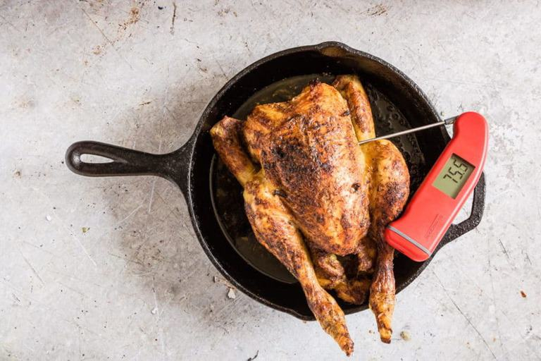 roast orange chicken recipe in a skillet with a thermometer to check the temperature