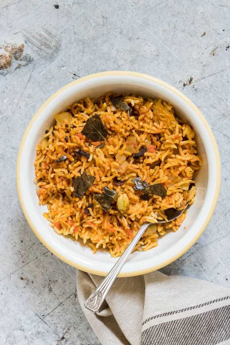 Over head shot of a bowl of south Indian tomato rice recipe with a spoon text in