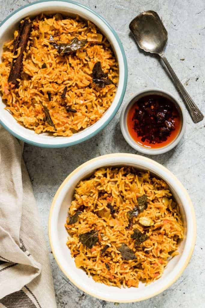 Overhead shot of two bowls of south Indian tomato rice recipe with chili sauce and a spoon