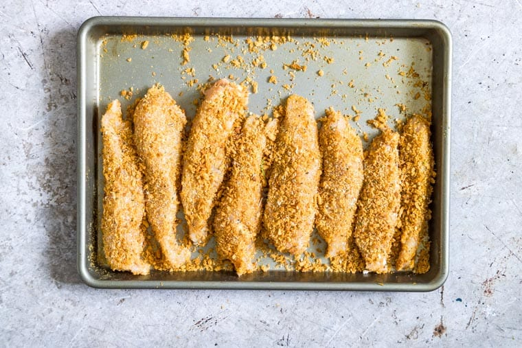 baking tray full of parmesan crusted chicken tenders ready to be cooked