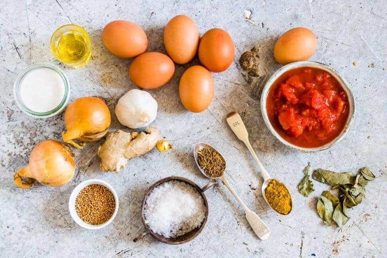 Ingredients for Indian egg curry recipe - eggs, chopped tomatoes, garlic, ginger, onions, oil, coconut milk, curry leaves, mustard seeds, curry powder and cumin seeds