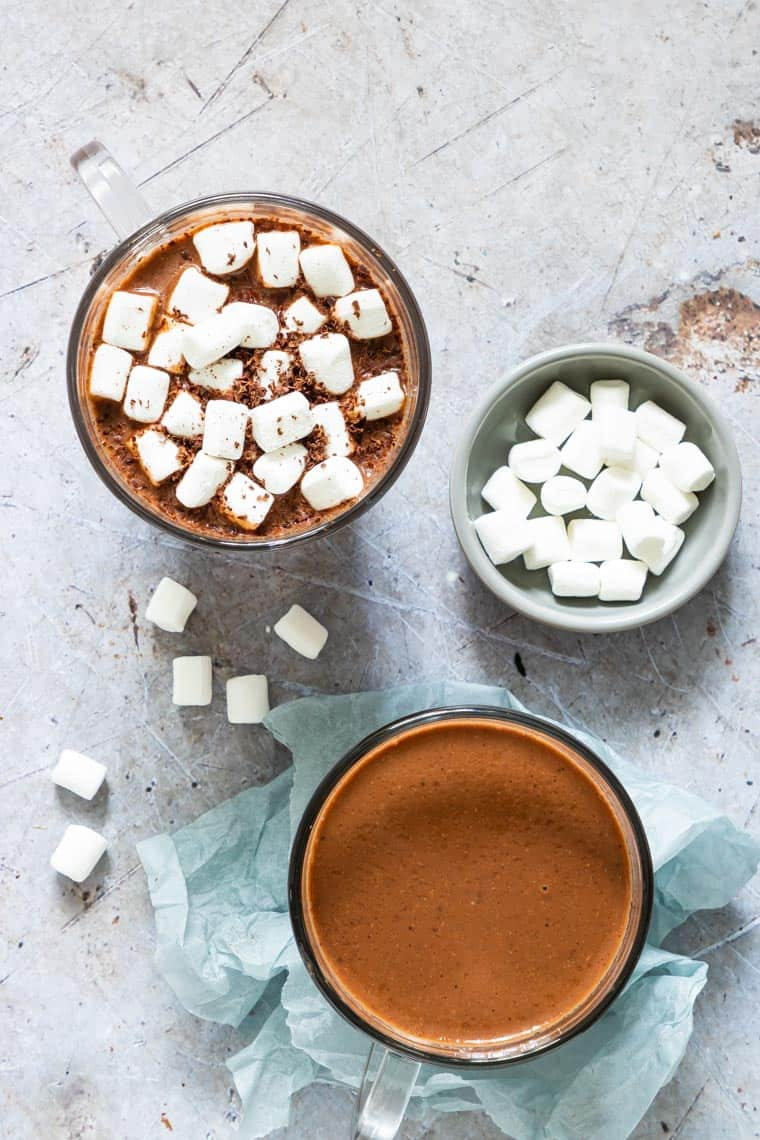 top down shot of 2 glasses instant pot hot chocolate with marshmallows surrounding them
