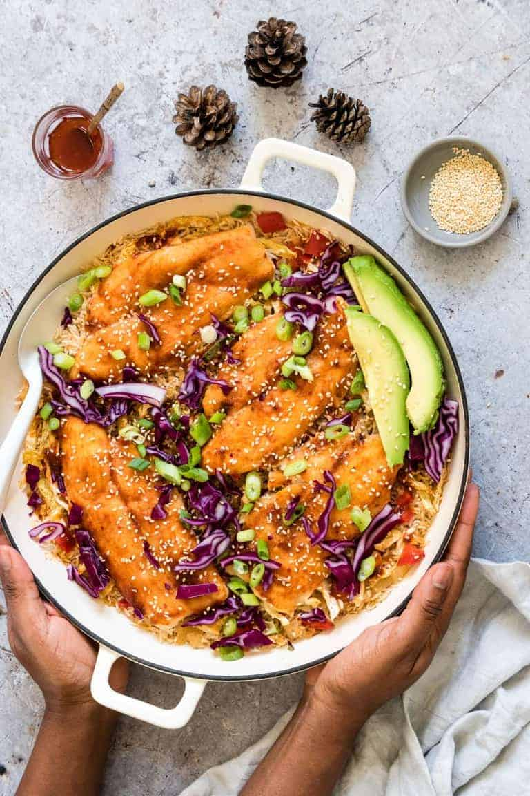 hands holding pot filled with asian rice and fish dish with avocado on top. On the sides are pine cones, bbq sauce and sesame seeds