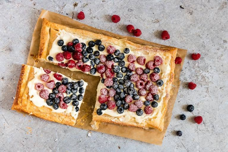 Berries and Cream Cheese Puff Pastry Breakfast Tart with some sliced off, and berries