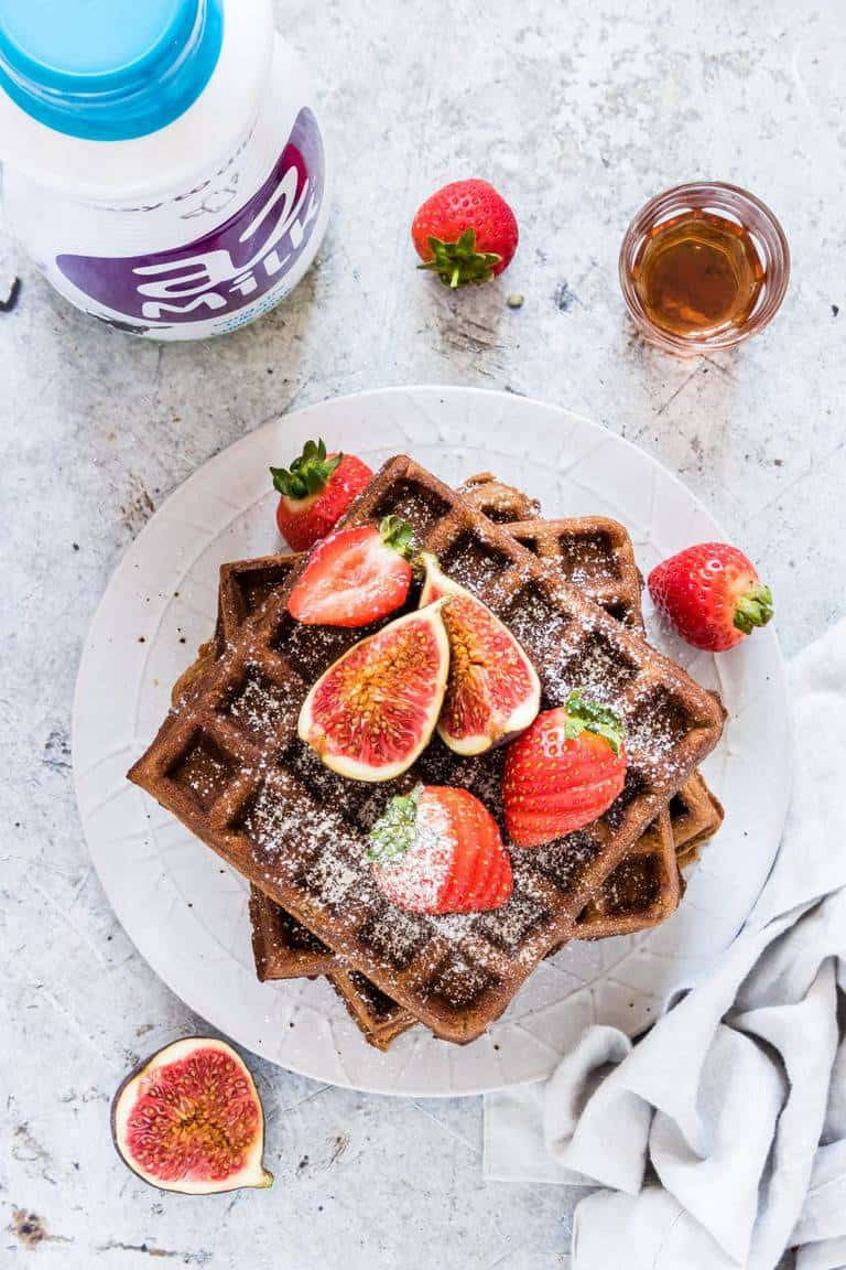 overhead view of stack of gingerbread buckwheat waffles on a white plate next to milk bottle, strawberries and maple syrup