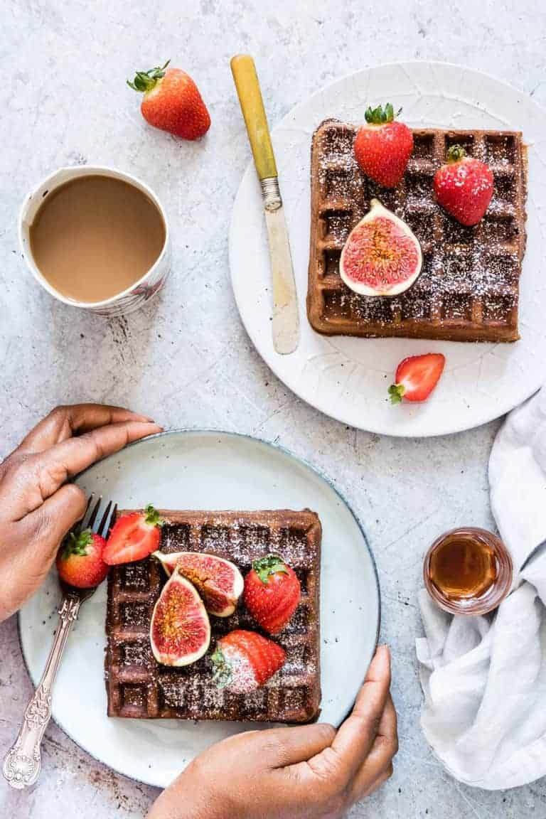 hand around plate containing gingebread buckwheat waffles next to cup of coffee and another plate with waffles, maple syrup and starwberries