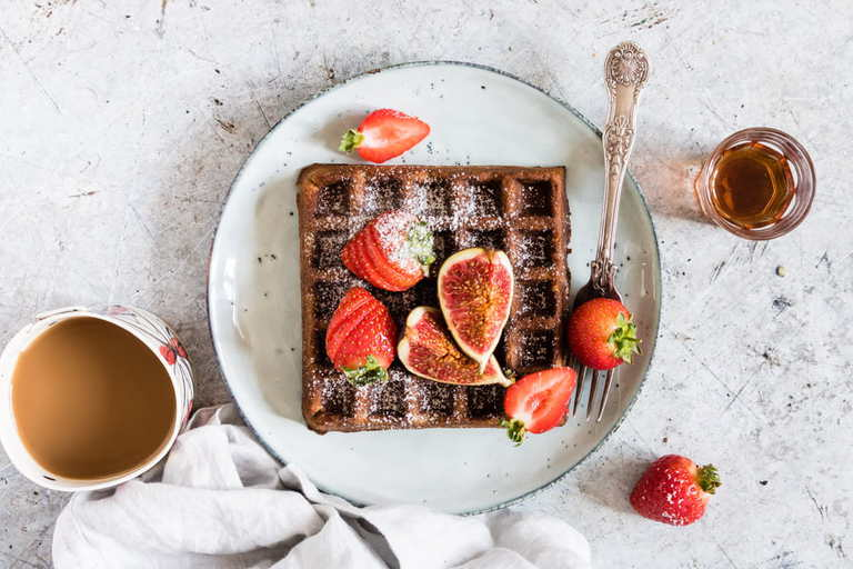 overhead view of gingerbread buckwheat waffles on a plate with a fork and chopped figs and strawberries and a cup of coffee