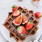 overhead view of gingerbread buckwheat waffles covered in figs and strawberries