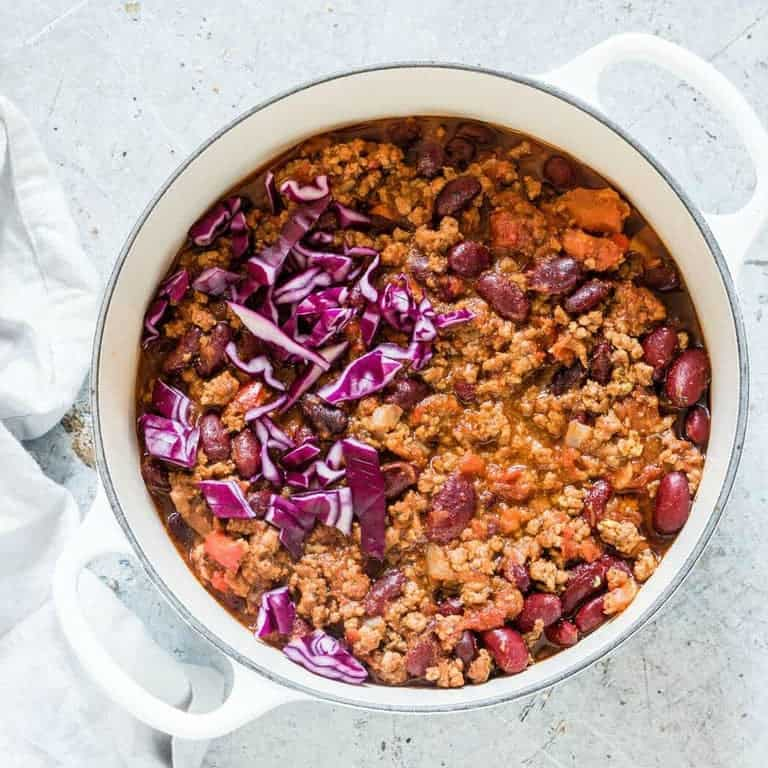 closeup of large pot of instant pot chilli with shredded cabbage on top