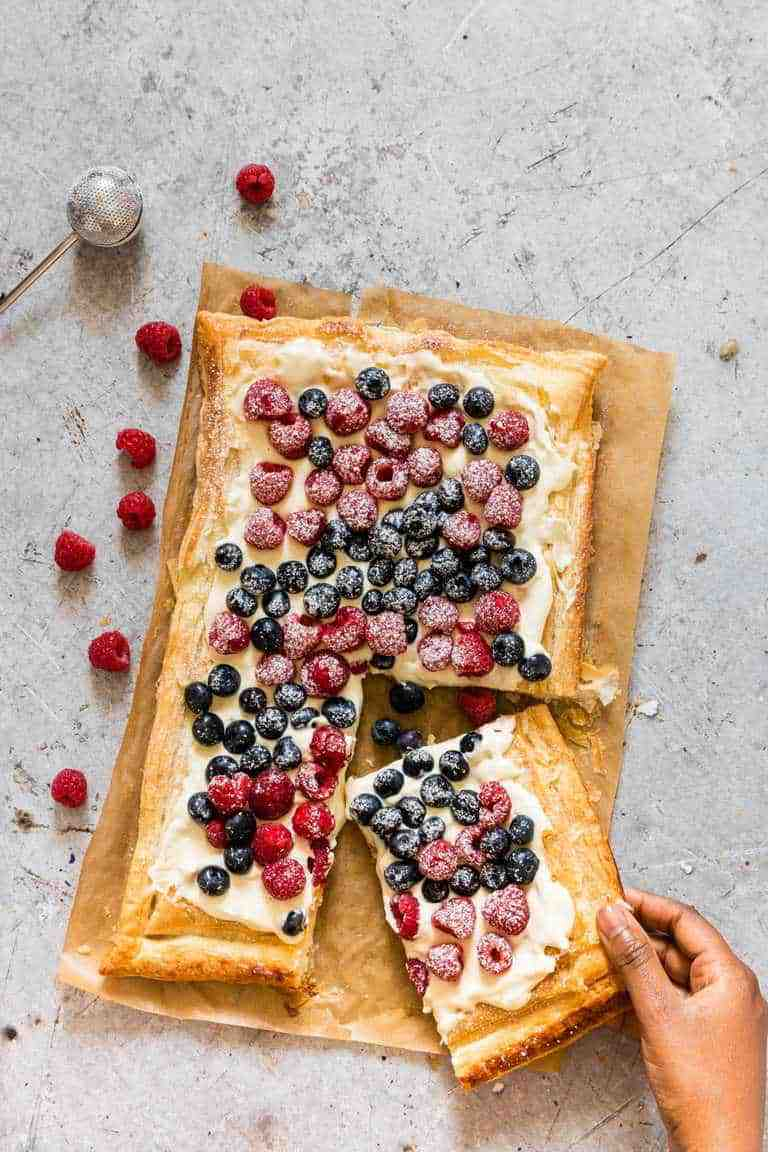 Berries and Cream Cheese Puff Pastry Breakfast Tart with a hand taking a slice, with berries