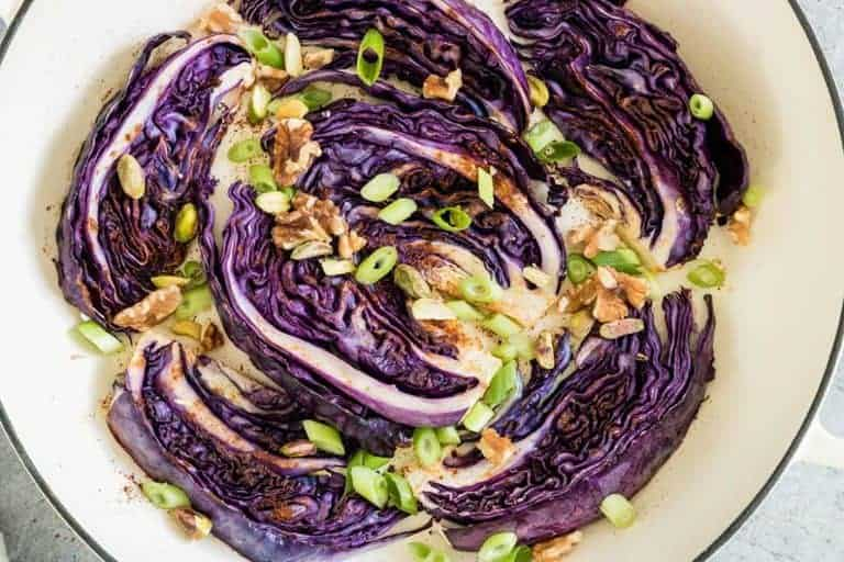 Roasted red cabbage in a pot with spring onions, walnuts and baharat spice