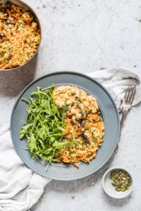Harissa hummus and roasted veg freekeh salad with rocket on a plate with pumpkin seeds in a bowl and freekeh salad in a pot. Cloth and fork on the side
