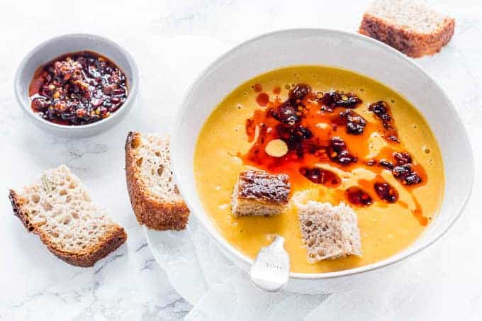 bowl of sweet potato and carrot soup next to slices of bread