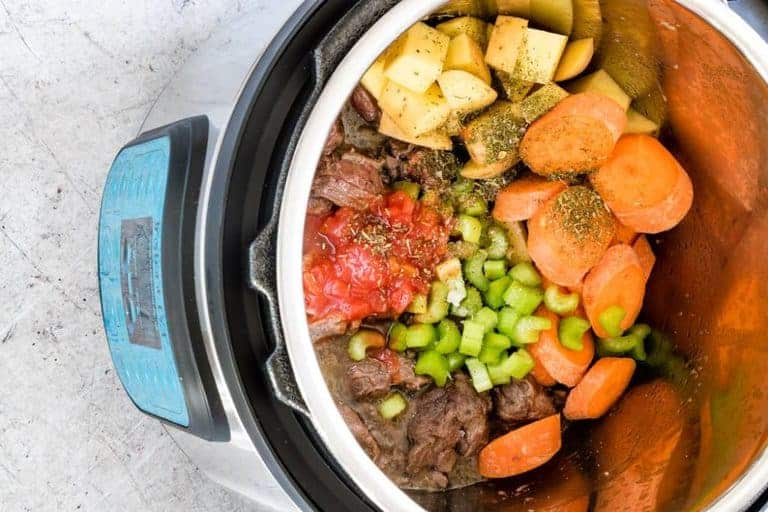 Ingredients For Instant Pot Beef Stew - potatoes, carrots, cooked beef, celery, oil, stock, tomatoes, herbs, salt, in the instant pot
