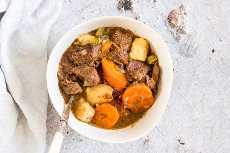 Pressure Cooker Beef Stew in a bowl with a spoon and cloth next to it