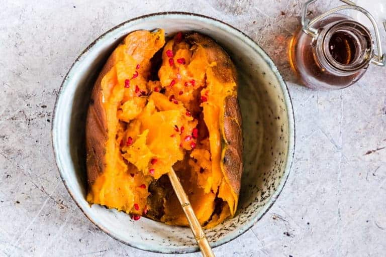 Instant Pot Sweet Potatoes in a bowl with maple syrup, raspberries and a spoon