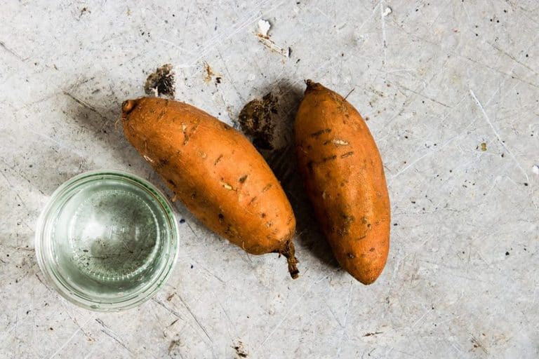 2 Sweet Potatoes For the Instant Pot and water on a table