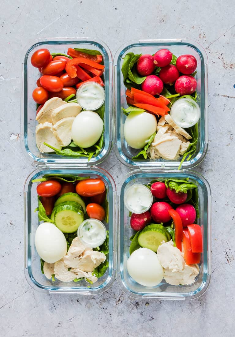 four meal prep containers filled with salad, tomatoes, hard boiled egg, and slices of Instant Pot chicken breasts