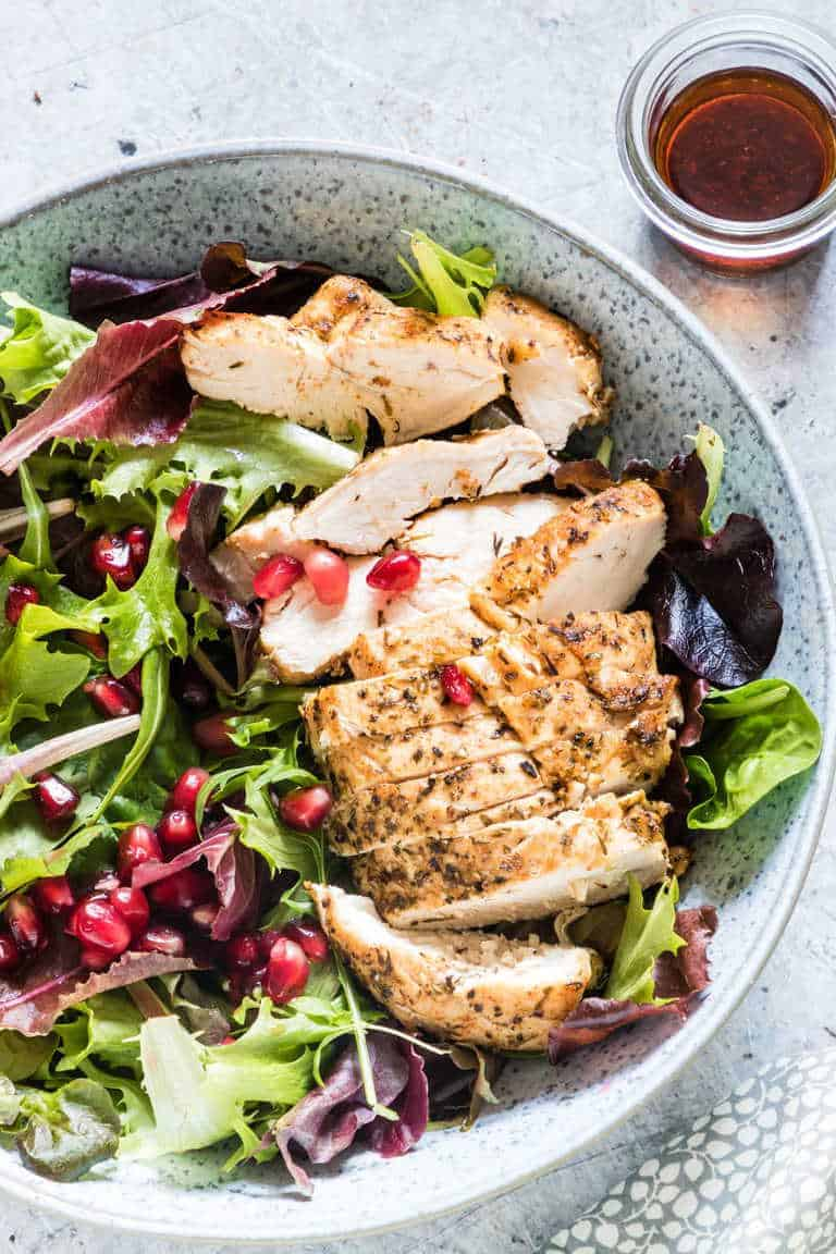 Overhead shot of a salad with slice chicken breast, salad greens and pomegranate