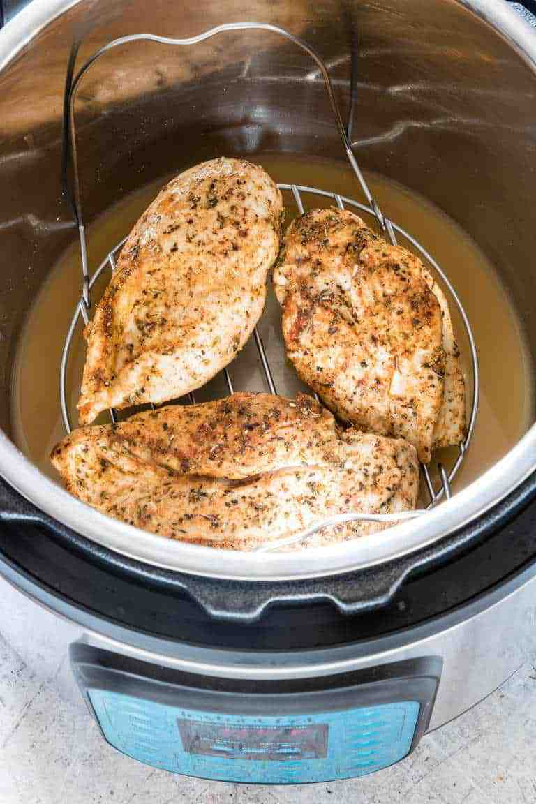 Three cooked chicken breasts in an instant pot on a trivet over some chicken stock