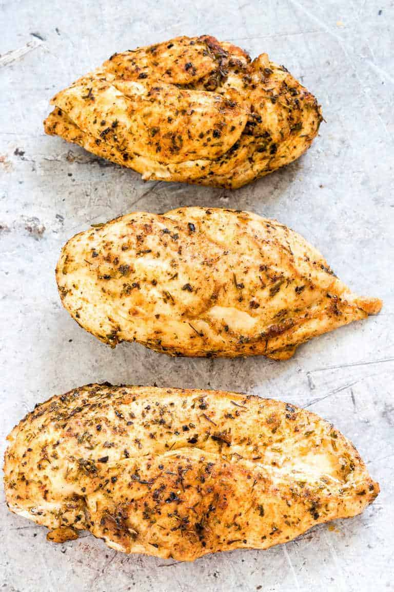 3 cooked chicken breasts on a grey background