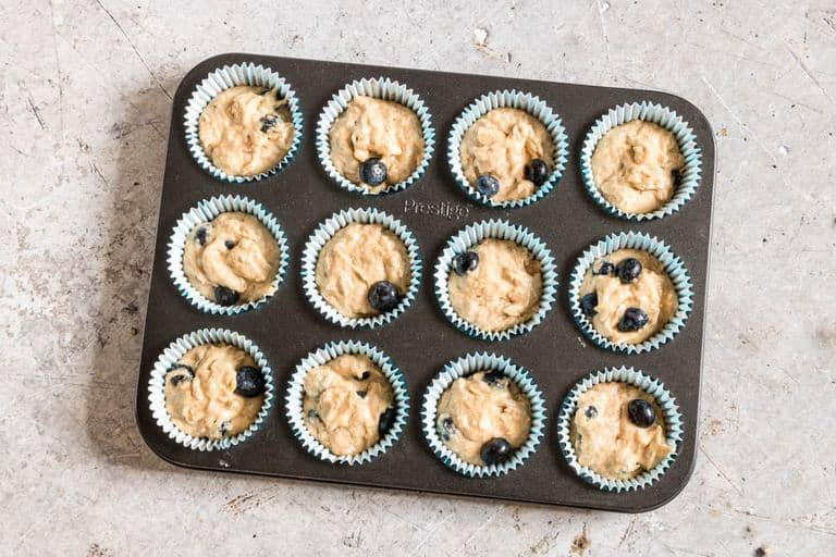 blueberry muffins in blue muffin liners in muffin tray