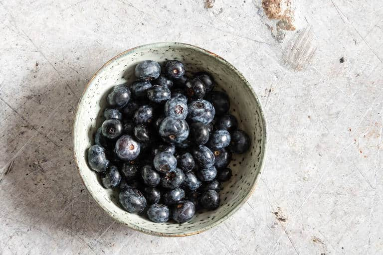 overhead shot of bowl containing bright and fresh blueberries