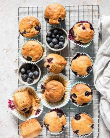 overhead shot of Vegan Blueberry Muffins with blueberries on a cooling rack with a cloth