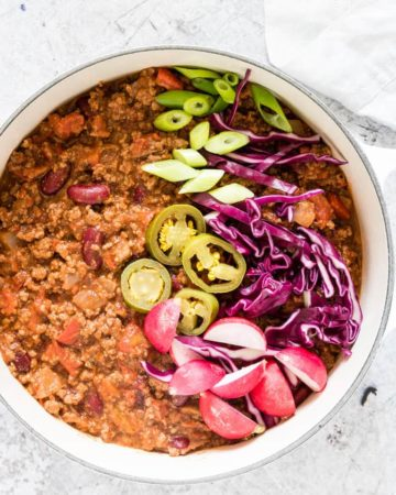 Overhead picture of cooked venison chilli in a white pot with spring onion, jalapenos, radishes and red cabbage as garnish