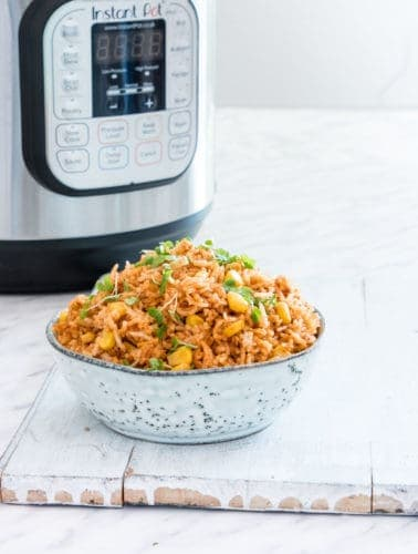 image of instant pot mexican rice in a bowl garnished with greens next to an instant pot