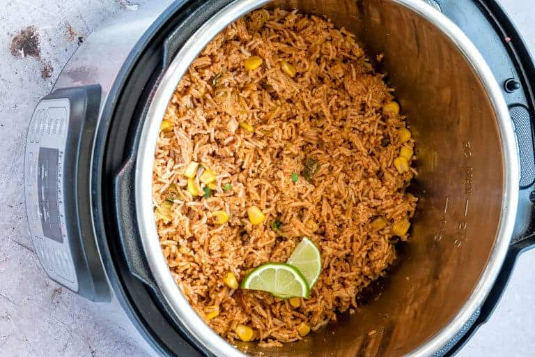 Landscape close up image of instant pot mexican rice in an Instant Pot garnished with greens