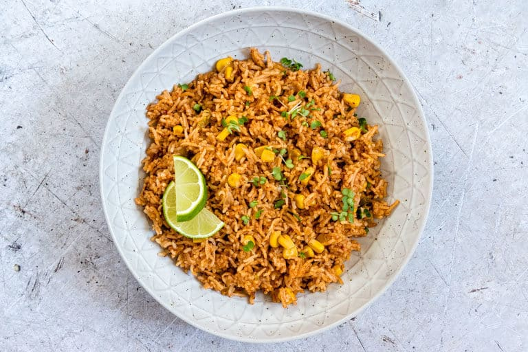 close up image of instant pot mexican rice in a bowl garnished with greens