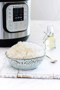 Bowl of instant pot white rice next to instant pot with seasoning and spoon