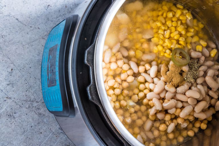 instant pot filled with uncooked ingredients for white chicken chili
