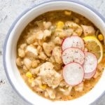 blue rimmed white bowl containing serving of white chicken chili with sliced radishes on top
