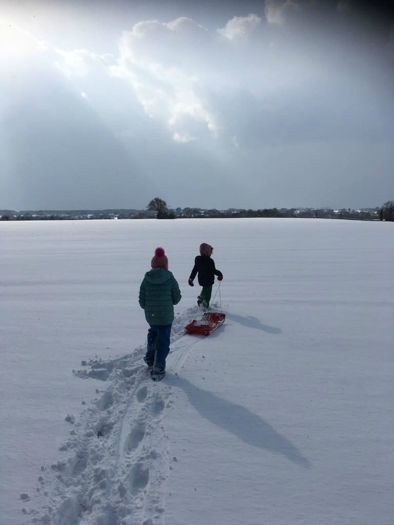 children playing in snow covered field before eating white chicken chili