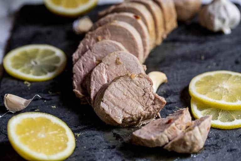 instant pot pork tenderloin in slices next to lemon and lime slices