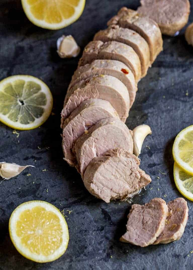 closeup of instant pot pork tenderloin cut next to lemons and limes
