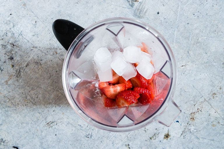strawberry daiquiri ingredients in a blender with ice on top