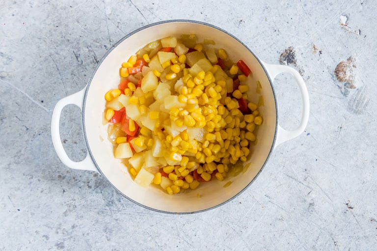 pineapple fried rice - pineapple, sweet corn, pepper and onions in a pot
