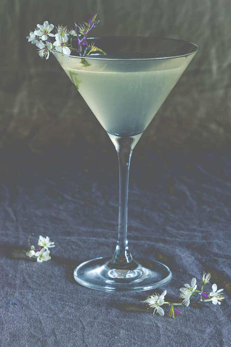 moody lemon drop martini surrounded by white flowers