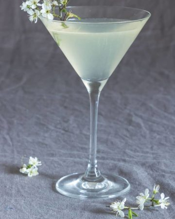 closeup of lemon drop martini on drop cloth surrounded by flowers