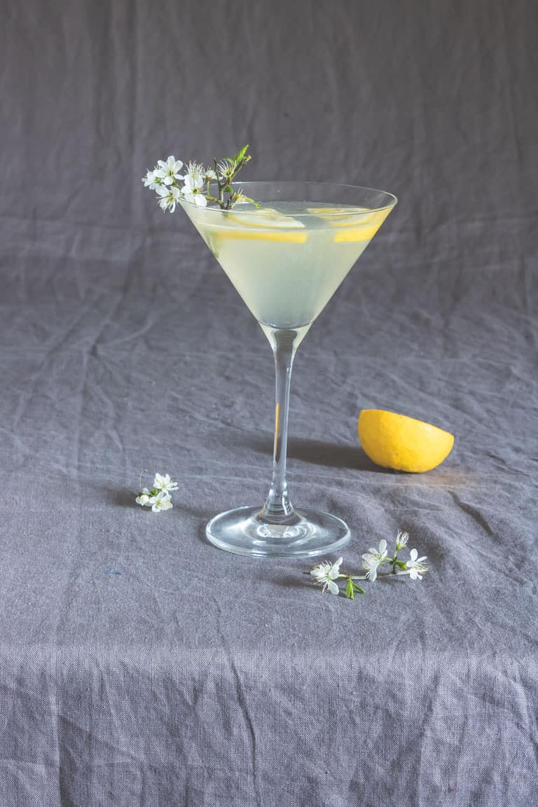 lemon drop martini on a table next to half of a lemon and flowers