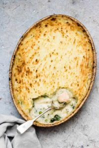 A fish pie with some scooped out with spoon and some fish on a table