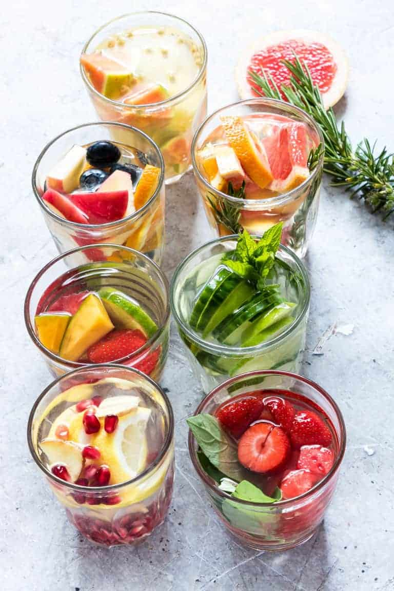 7 glasses full of differnet fruity infused waters